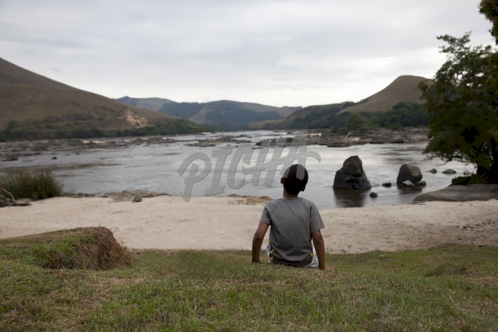 Boy looking at view of Ogoue river in Lope, Gabon