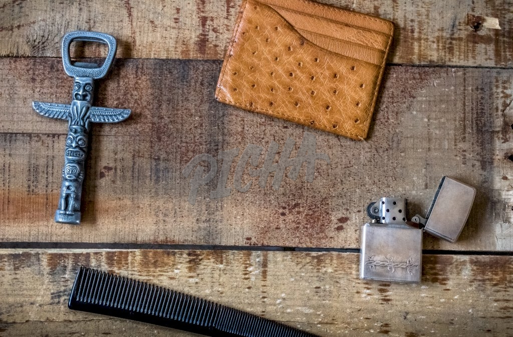 men accessories with lighter, bottle opener, comb and card wallet on wooden background