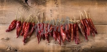 String of dried red chili peppers on wooden background