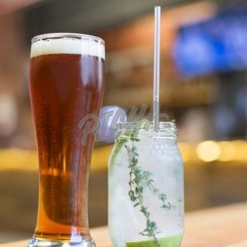 Glass of beer next to a cocktail jar