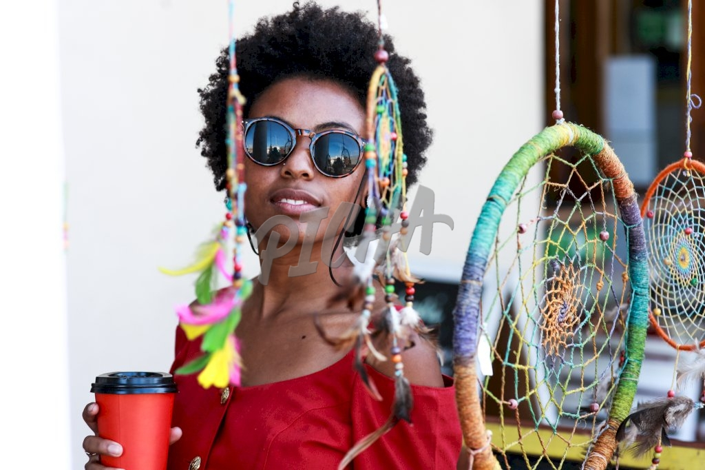Afro woman holding a coffee cup