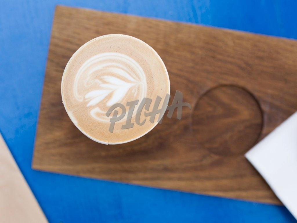A cup of latte on a wooden board
