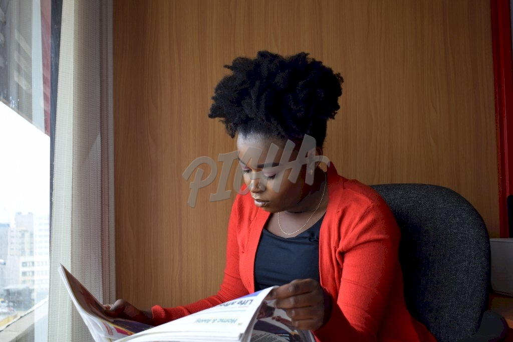 Woman reading newspaper in the office