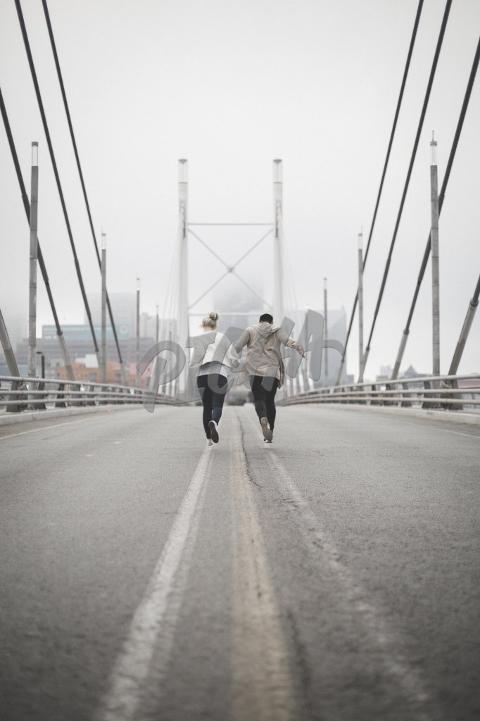 Two people running over a bridge
