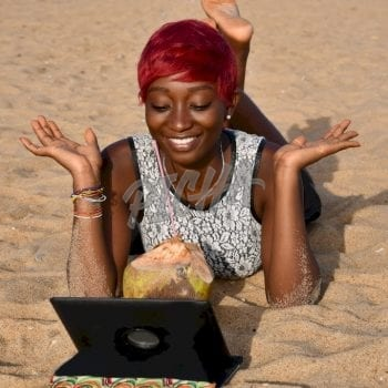 Woman watching on a tablet at the beach in Lome, Togo