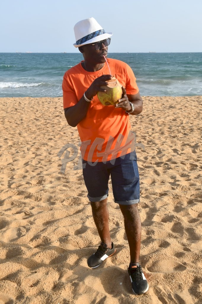 Man drinking coconut water at the beach in Lome, Togo