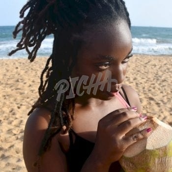 Woman drinking coconut water at the beach in Lome, Togo