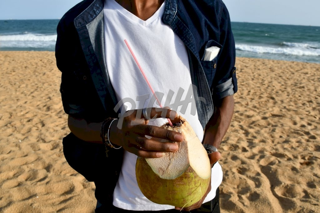 Man holding a coconut in Lome, Togo