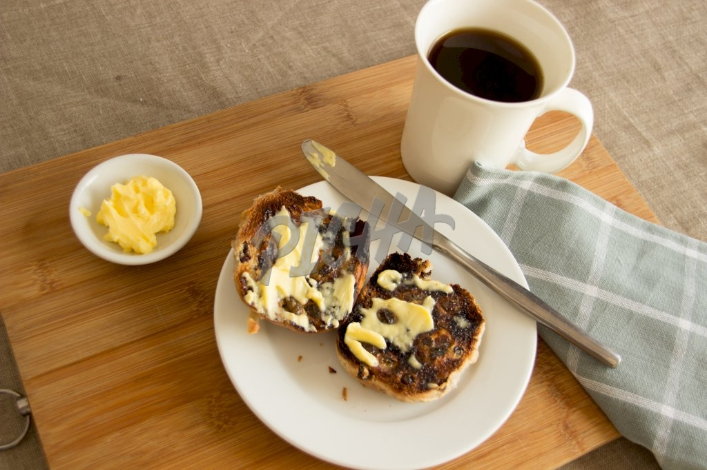 Toasted bun with butter and coffee, high-angle view