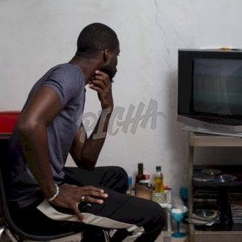Man watching TV at home in Libreville, Gabon