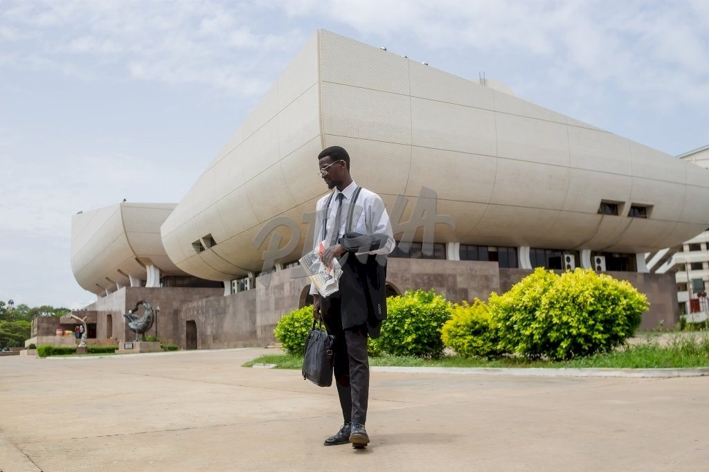 Man standing in front of the National Theatre of Ghana