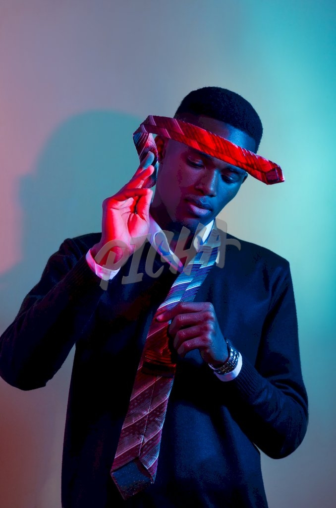 Putting on a tie under creative lighting, Accra, Ghana