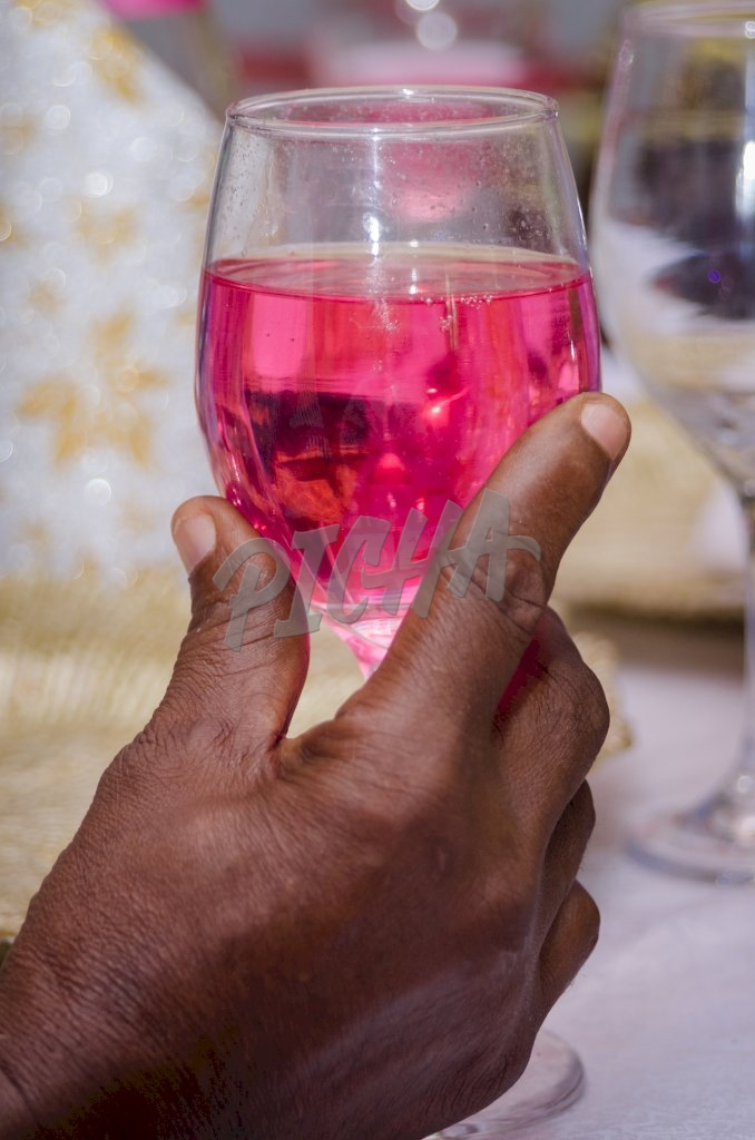 Hand with glass of pink cocktail