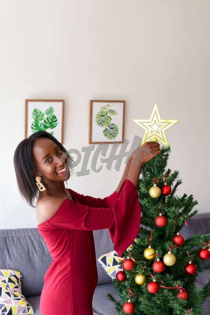 Young woman arranging Christmas tree
