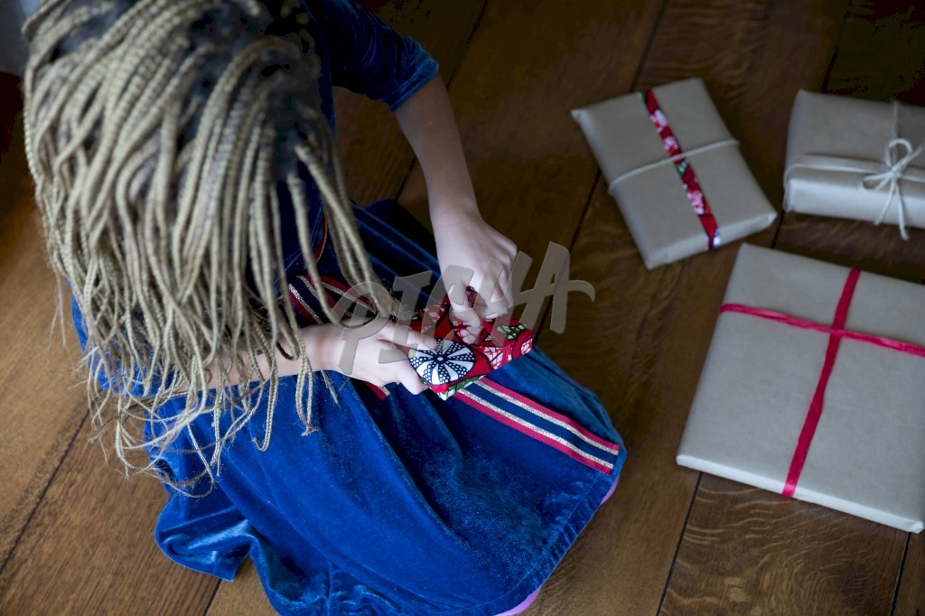 braided girl opening a gift