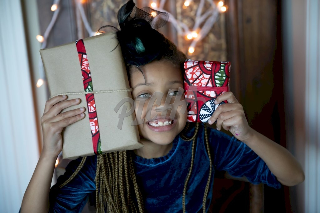 Dressed up girl holding gifts