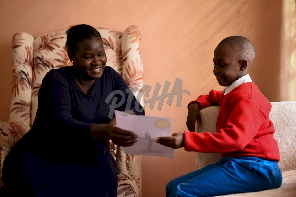 Boy sharing drawing with mother