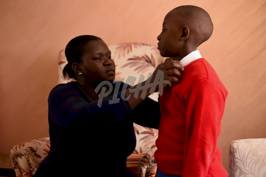 Mother helping son getting ready for school