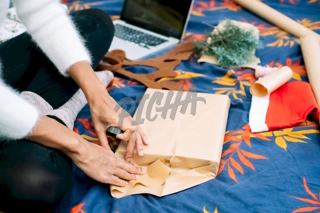 Young woman wrapping a gift for christmas