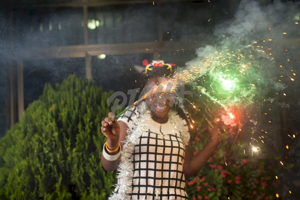Cheerful young woman holding sparklers in Accra, Ghana