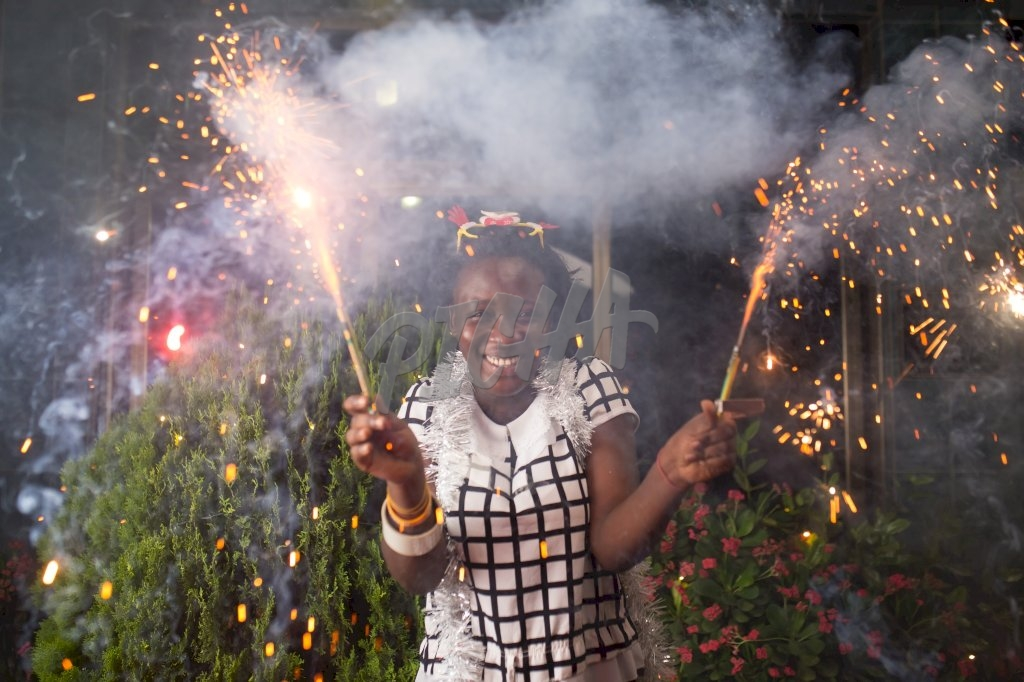 Cheerful young woman holding sparklers