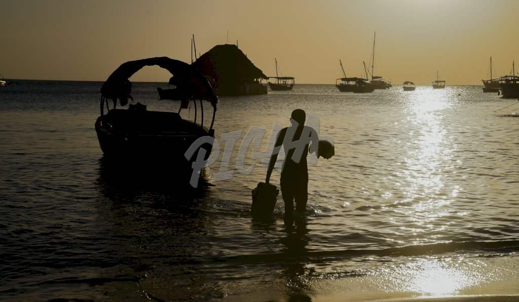 Boats and sunset make backdrop for man walking onto shore