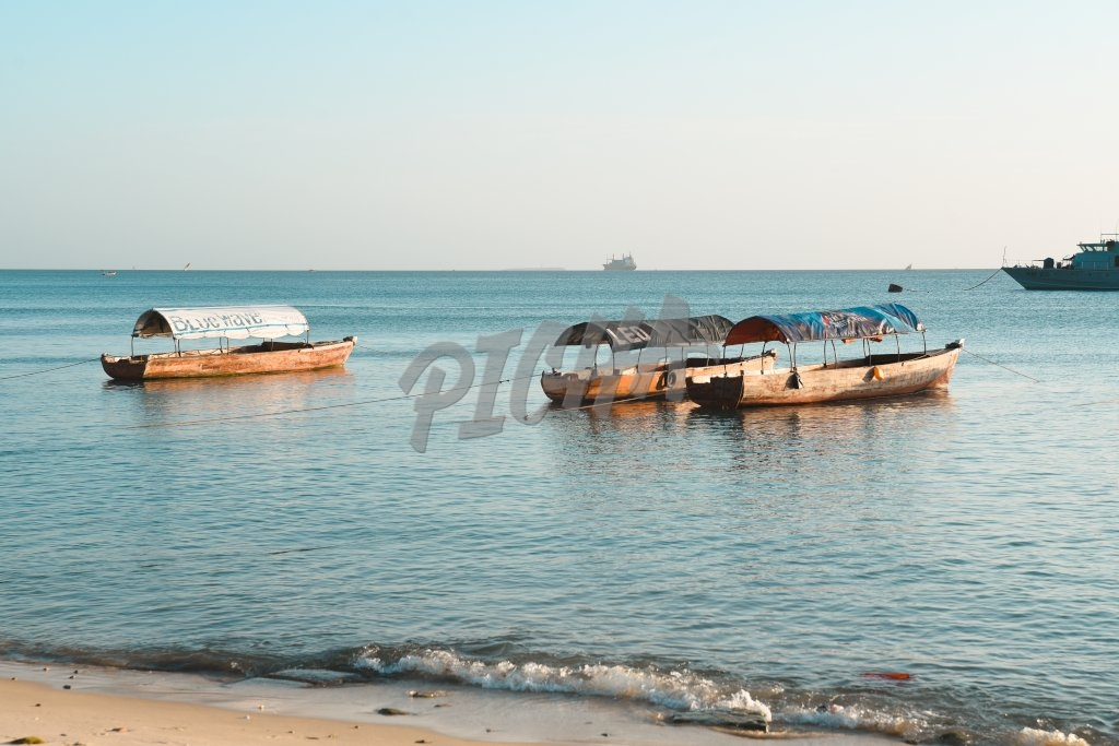 Three boats lay anchored just off the shore