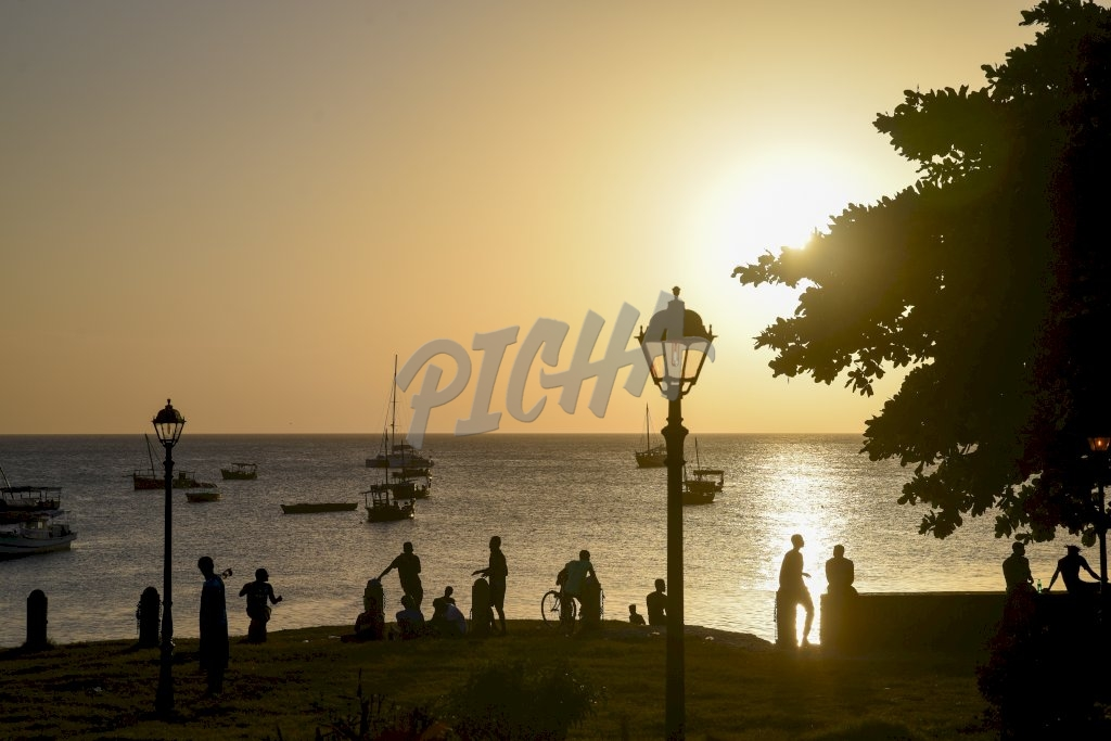 small groups of people gathered by the ocean as the sun sets