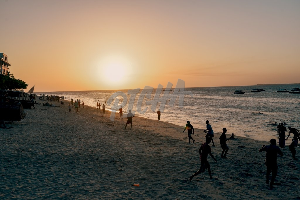 a group of people have fun playing games on the beach at sunset