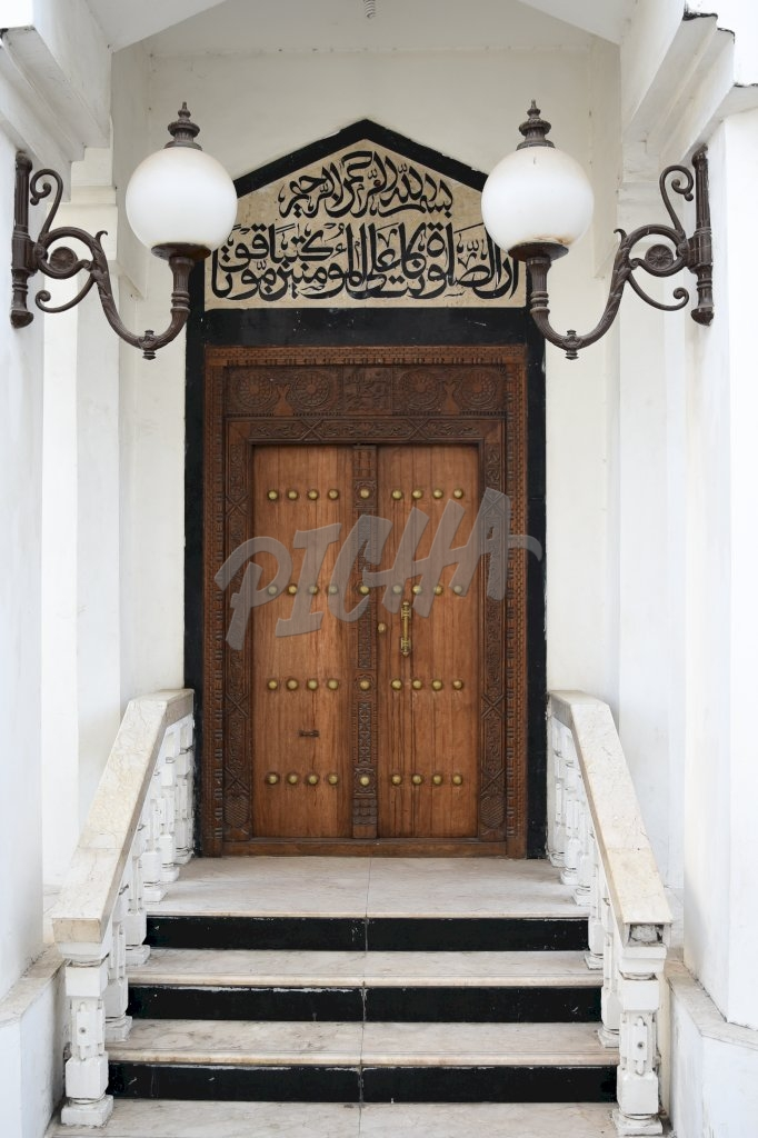 Arabic inscriptions sit atop an antique style wooden door with intricate carvings