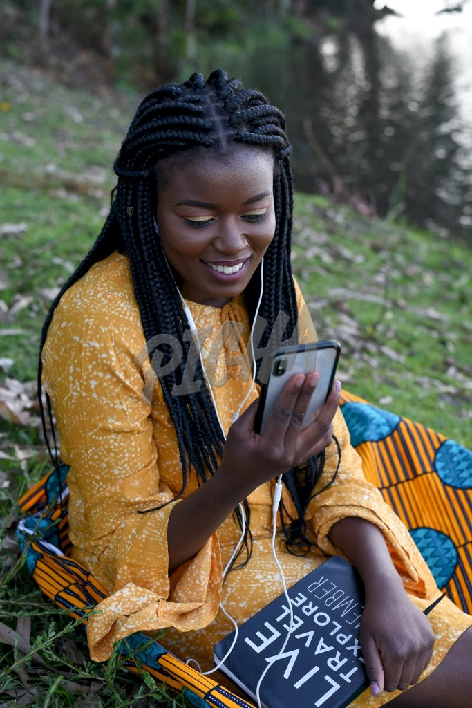 Woman sitting on grass on her phone