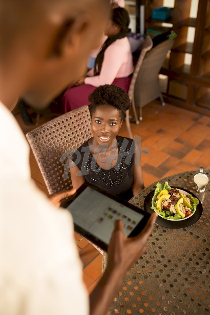client watches as waiter employs the aid of a tablet to process their transaction