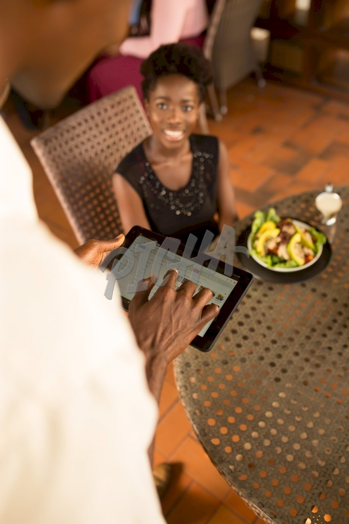 waiter employs the aid of a tablet to process transaction