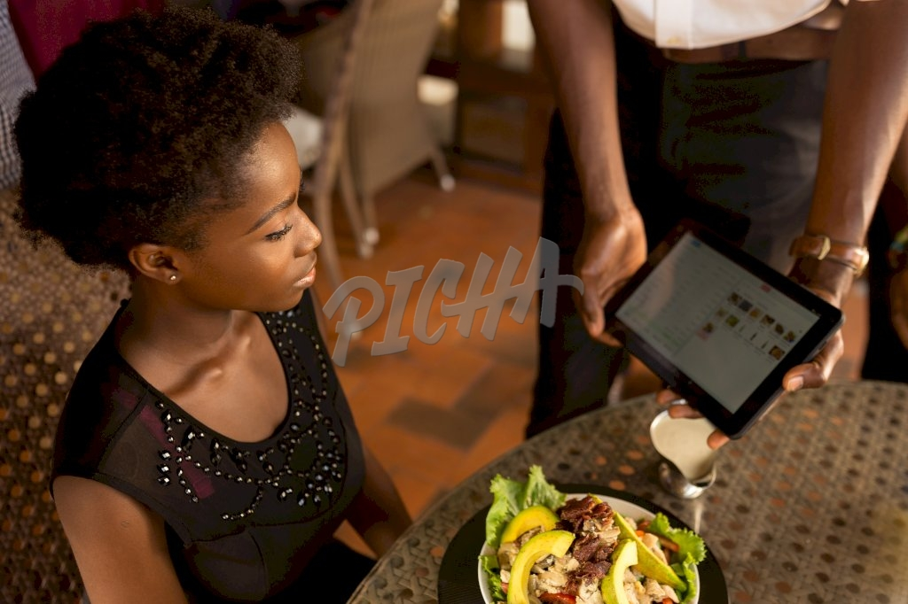 waiter employs the aid of a tablet in showcasing to a client