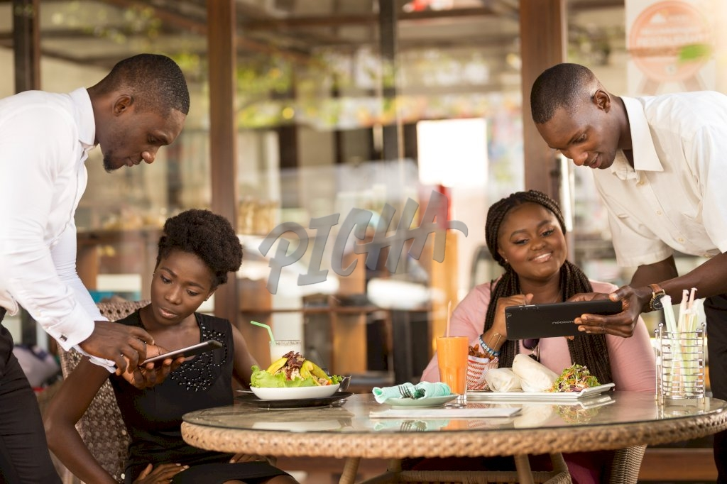 male waiters show what is on offer to two female clients