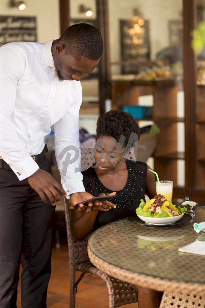 store attendant processes transaction on tablet for dining client