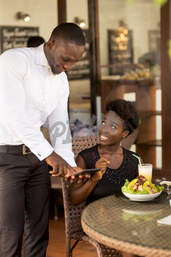 store attendant cordially processes transaction on tablet for dining client