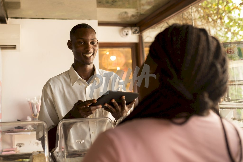 store attendant cordially processes transaction for client on tablet