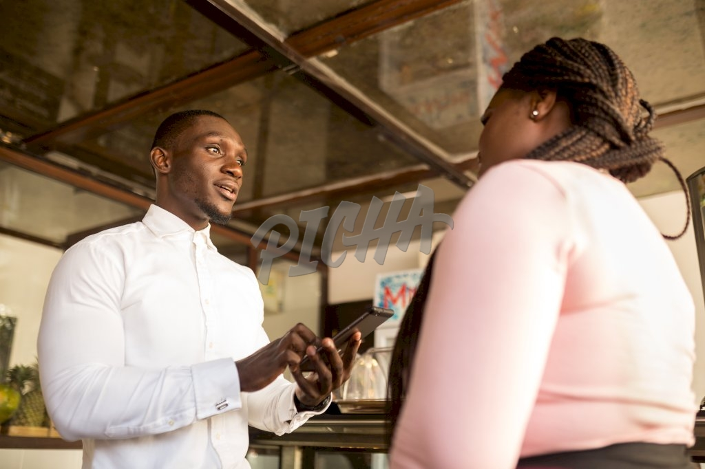 man processes transaction on tablet for lady