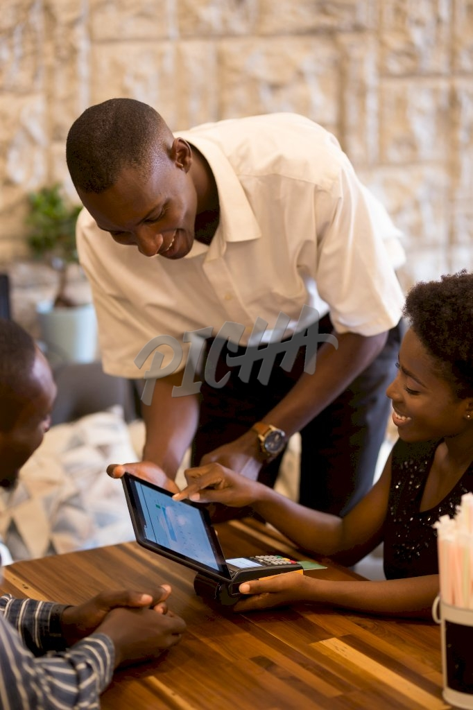 waiter serves couple with the bill