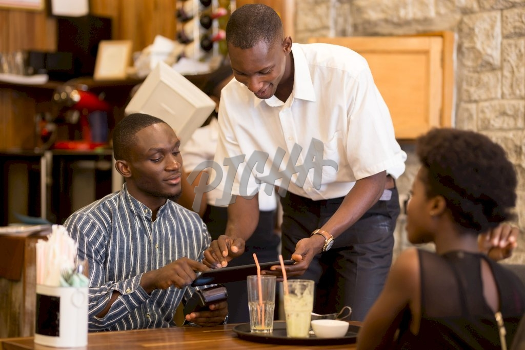 waiter serves couple with the bill after they finish their refreshments