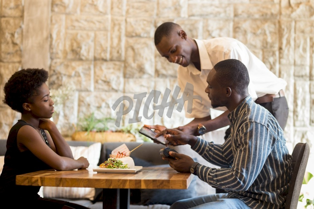 waiter gives service to a young couple at restaurant