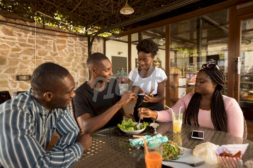 Lady offers service to man and two companions at a restaurant