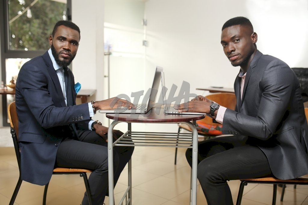 Young professional men share a work station