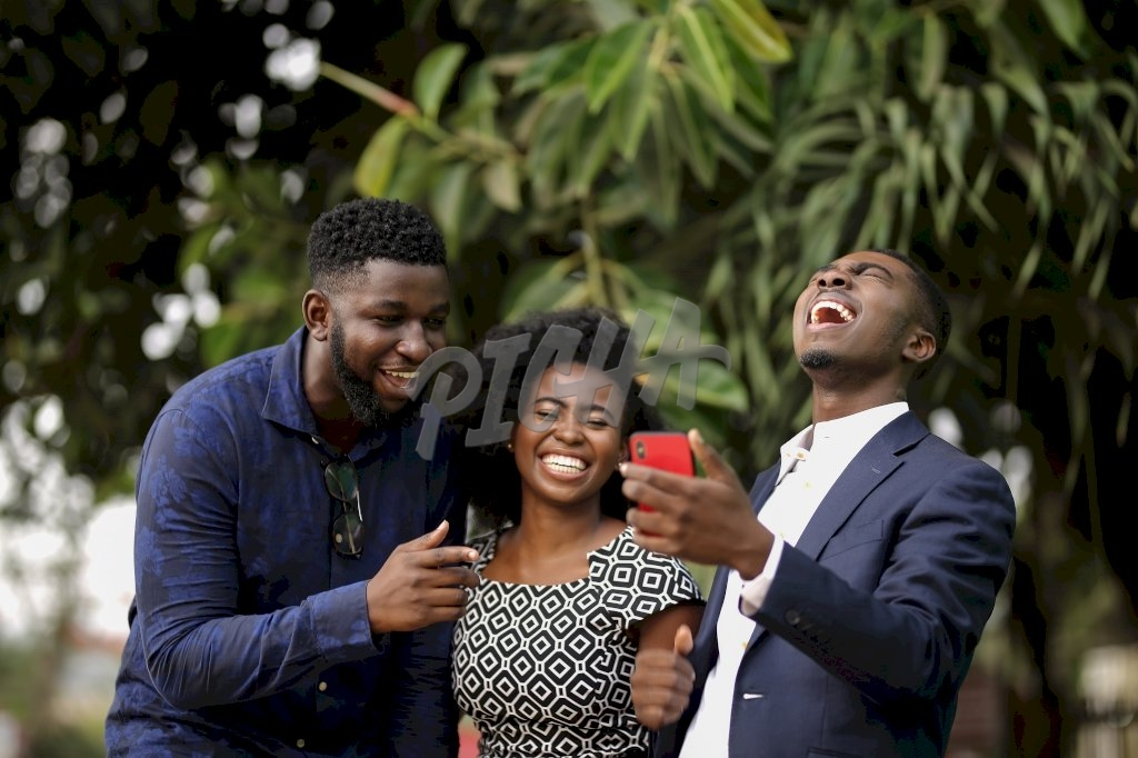 Young people share a joke on mobile phone and laugh