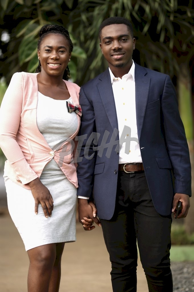 Smart young man and woman smile while holding hands outdoors