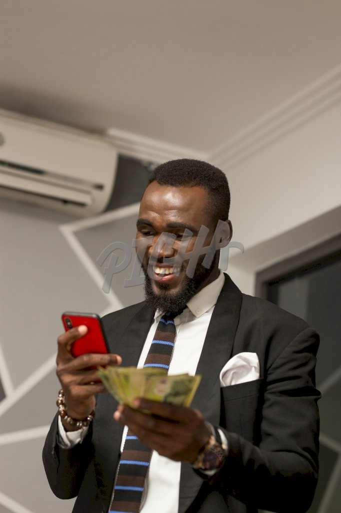Smiling business man holding phone and money