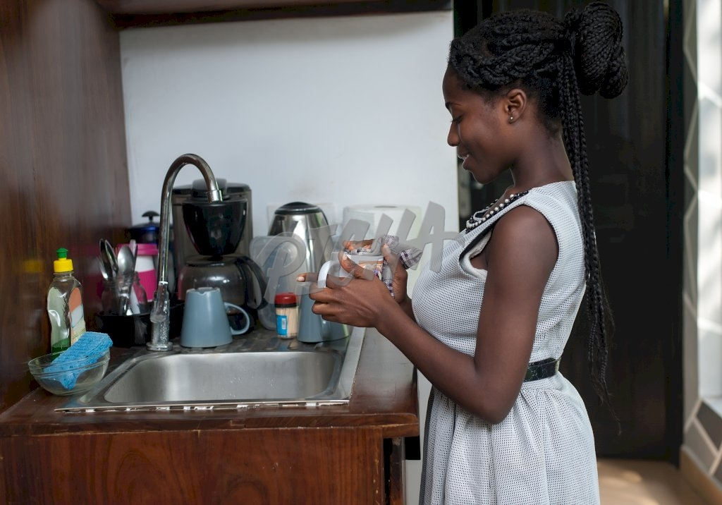 Lady in white dress grabbing a mug by the sink