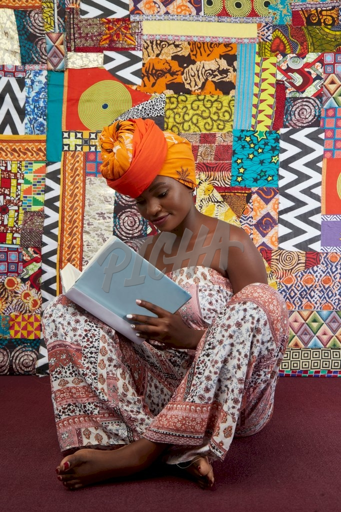 Gorgeous lady in jumpsuit and head wrap gleefully sits with her legs crossed reading a book