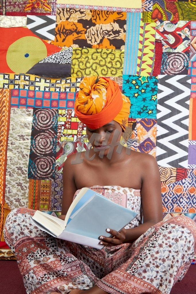 Gorgeous lady in jumpsuit and head wrap sits with her legs crossed reading a book